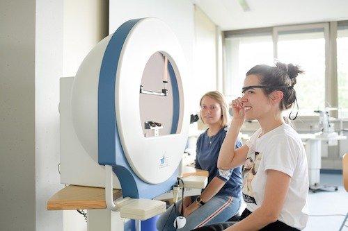 Zwei Schülerinnen der Fachschule für Augenoptik bereiten sich auf eine Perimetrie als Bestandteil eines Glaukomscreenings vor.
