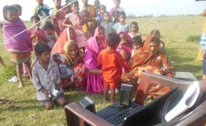 Women from Bhojpuri community enjoying a radio program in the bank of the River Brahmaputra, while they had come for an immunization camp conducted by the Dibrugarh Boat Clinic