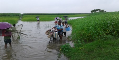 Members of the Dhubri Unit I on way to a health camp wading through flood water.