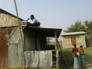 Solar lights being fitted at a river island village in lower Assam's Nalbari district
