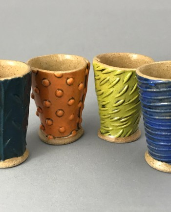 4 handmade 2oz shot glasses in a line