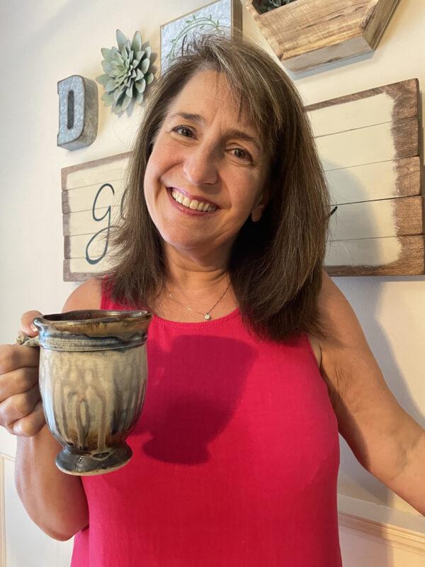 handmade ceramic mug held by friend