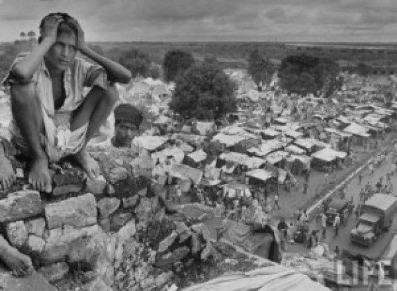 A youth sitting on the wall of Purana Qila with the uncertainty of future. The Purana Qila of Delhi was converted into a refugee camp for Muslims en route to Pakistan. © Margaret Bourke-White.