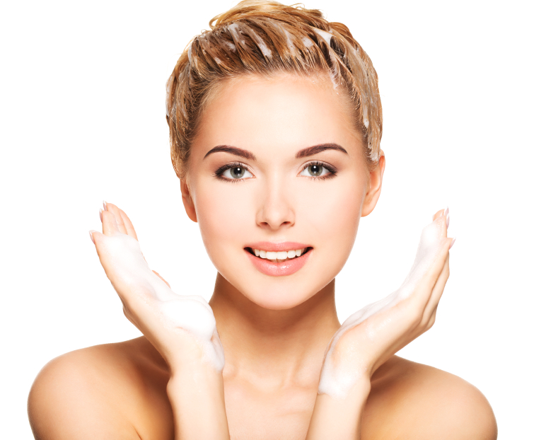 Portrait of a smiling young woman washing her hair on a white background