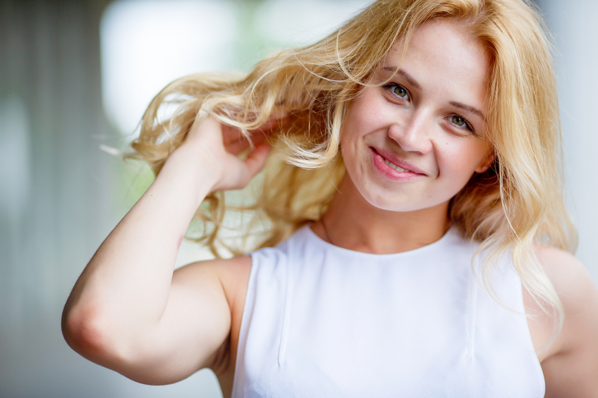 Blonde woman with long healthy curly blowing hair