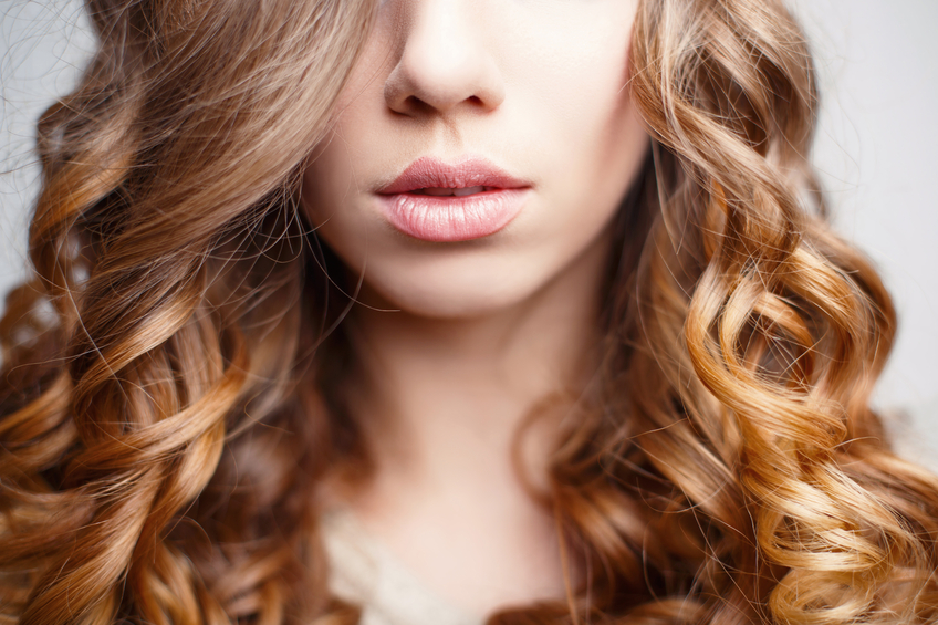 Beautiful pink lips close-up. Girl with curly hair