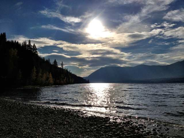 Places & Activities beautiful lakefront view at sunset with mountains by the surrounding areas