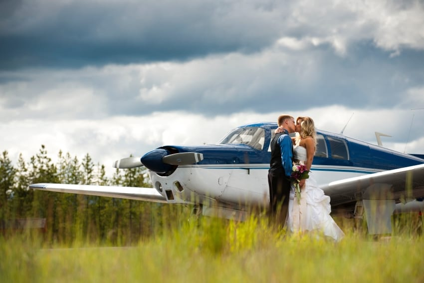 newly wed couple kissing in front of a plane at Cabin Creek Landing B&B