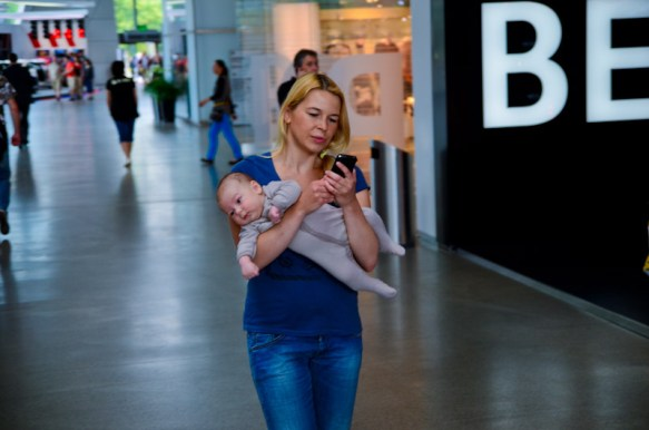 woman texting while carrying the baby-1