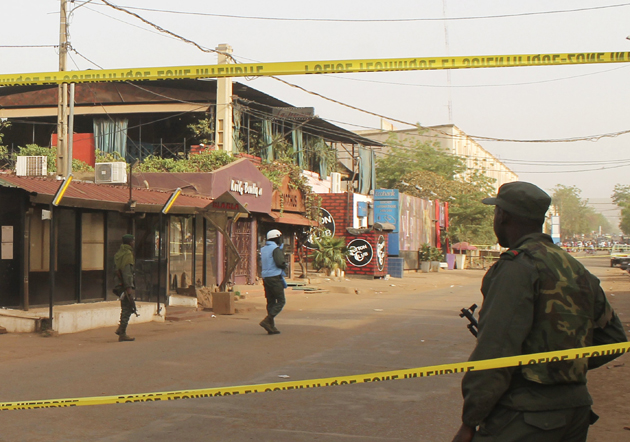 A soldier stands outside La Terrasse restaurant (top C) where militants killed five people, including a French citizen and a Belgian citizen, in a gun attack in Bamako