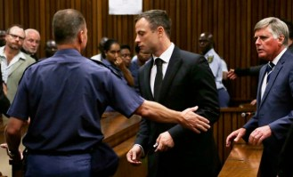 South African Olympic and Paralympic track star Pistorius is led to holding cells after he was sentenced at the North Gauteng High Court in Pretoria