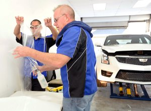 """Large sections of film, typical of most cars' and trucks' front end kits require two people for installation. Shown here, Is Bill DeBever (right) applying the Xpel """"secret sauce"""" which makes repositioning the film during installation possible. Knowing how to mix it and how much to use is one of the """"tricks"""" Xpel factory-trained installers learn. Image: Author."""