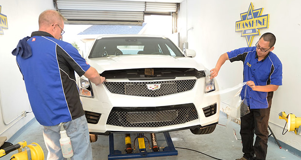 """Xpel-trained installers, Bill DeBever (left) and Jesus Dominguez. hang the largest piece of the Xpel Ultimate """"bumper kit"""" on the V-Net's ATS-V project. This part of the installation requires two people. Image: Author."""