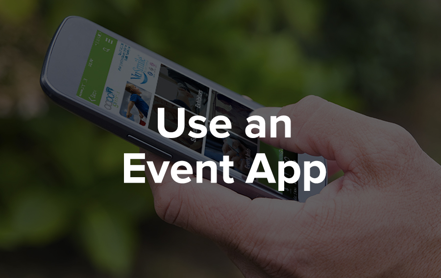 Someone holds an iPhone with an event app on the screen in their hand. They are outside in a sunny, green environment. That conference must have been really great because they're still interacting with the content and connecting with people through the app even after the meeting is over.