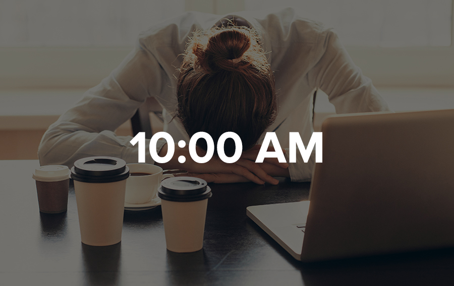 A meeting planner lays her head at her desk surrounded by four cups of coffee.