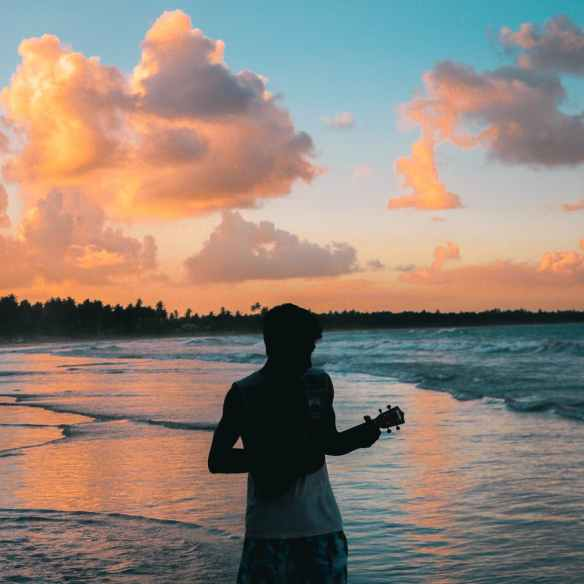 photo of man playing ukulele on seashore