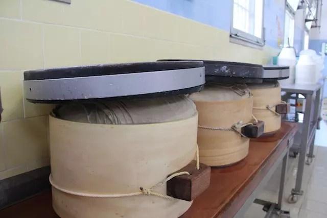 queijo sendo prensado para manter o seu formato original do ano de 1200.