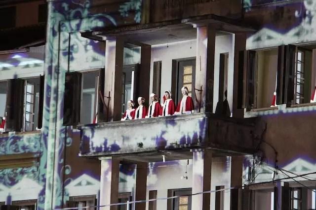 as crianças cantando da janela do prédio que ganha projeções