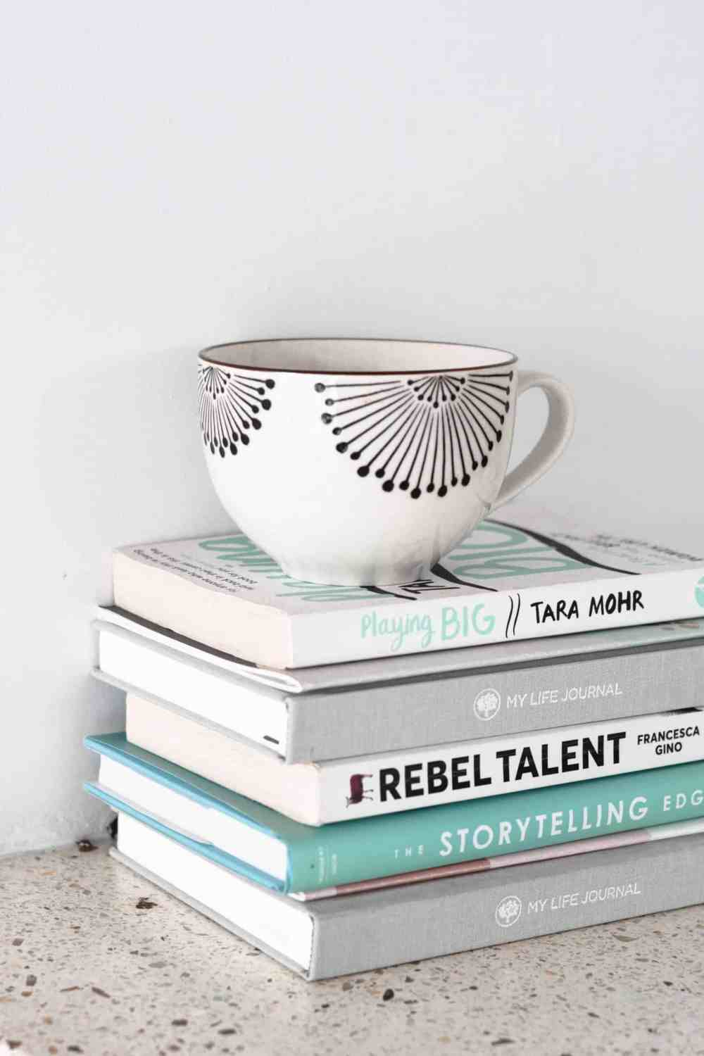 A stack of books with a coffee cup sitting on top