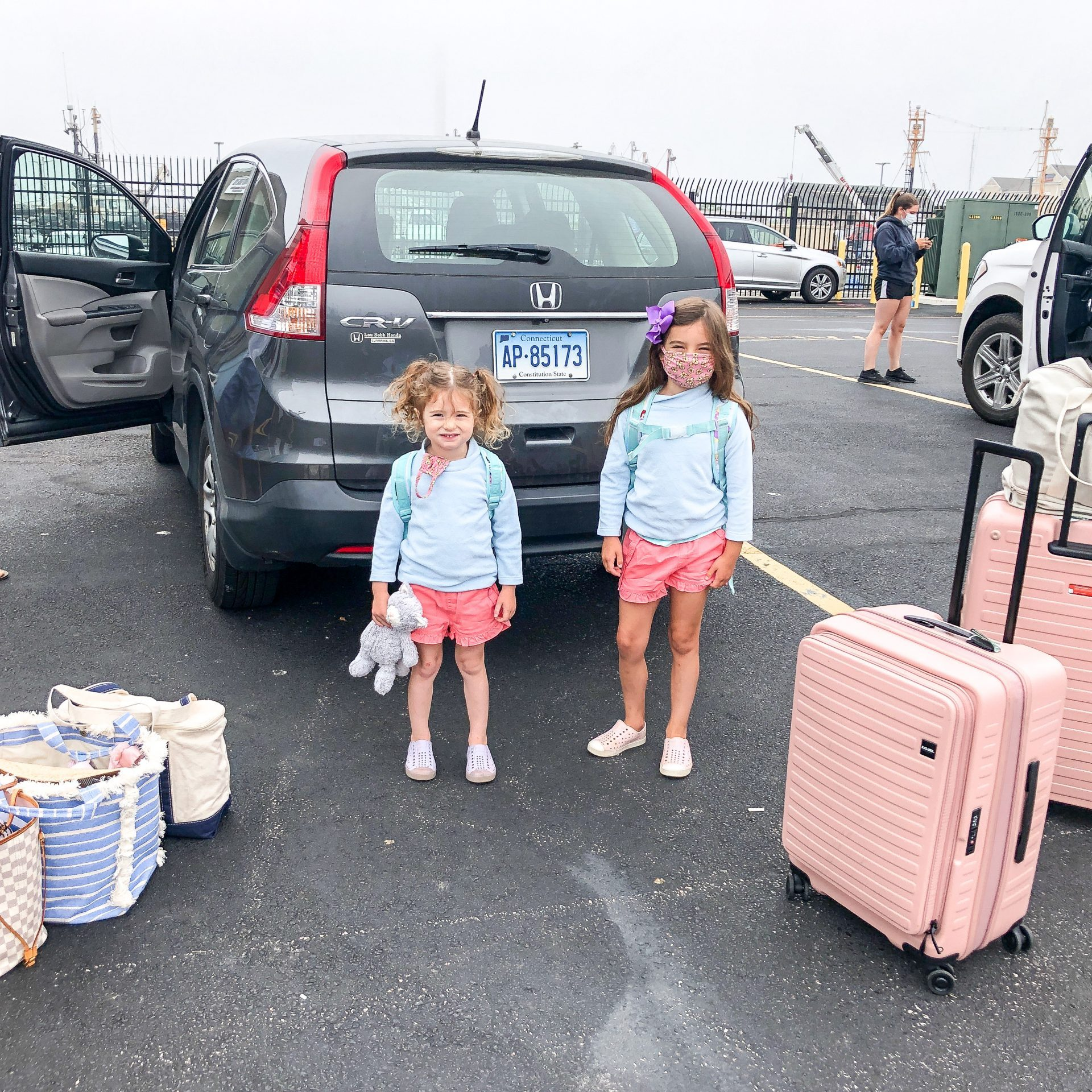 little girls with luggage and covid masks at Seastreak valet parking