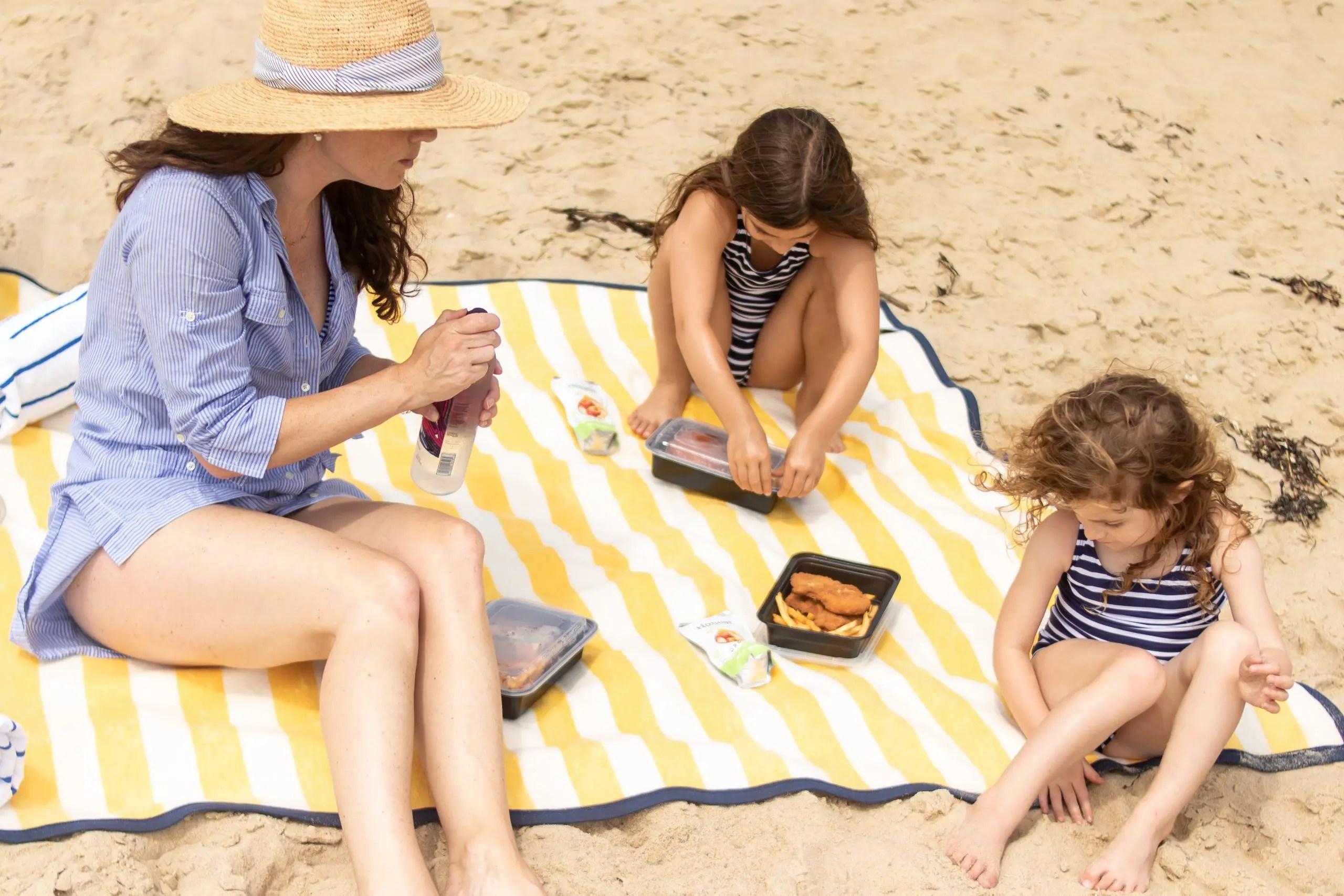 Family eating Winnetu Oceanside Resort Picnic Lunch on the Beach