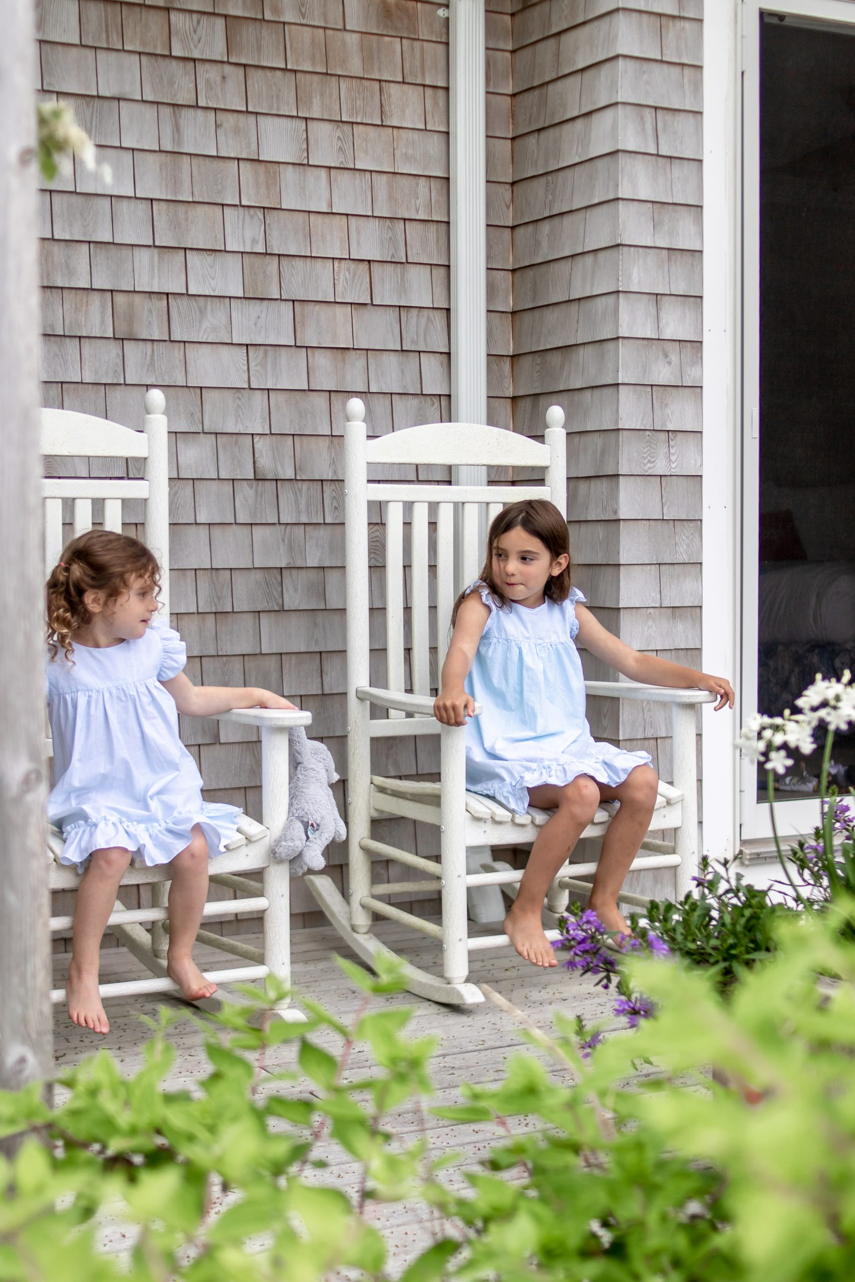 little girls in rocking chairs on cottage deck martha's vineyard