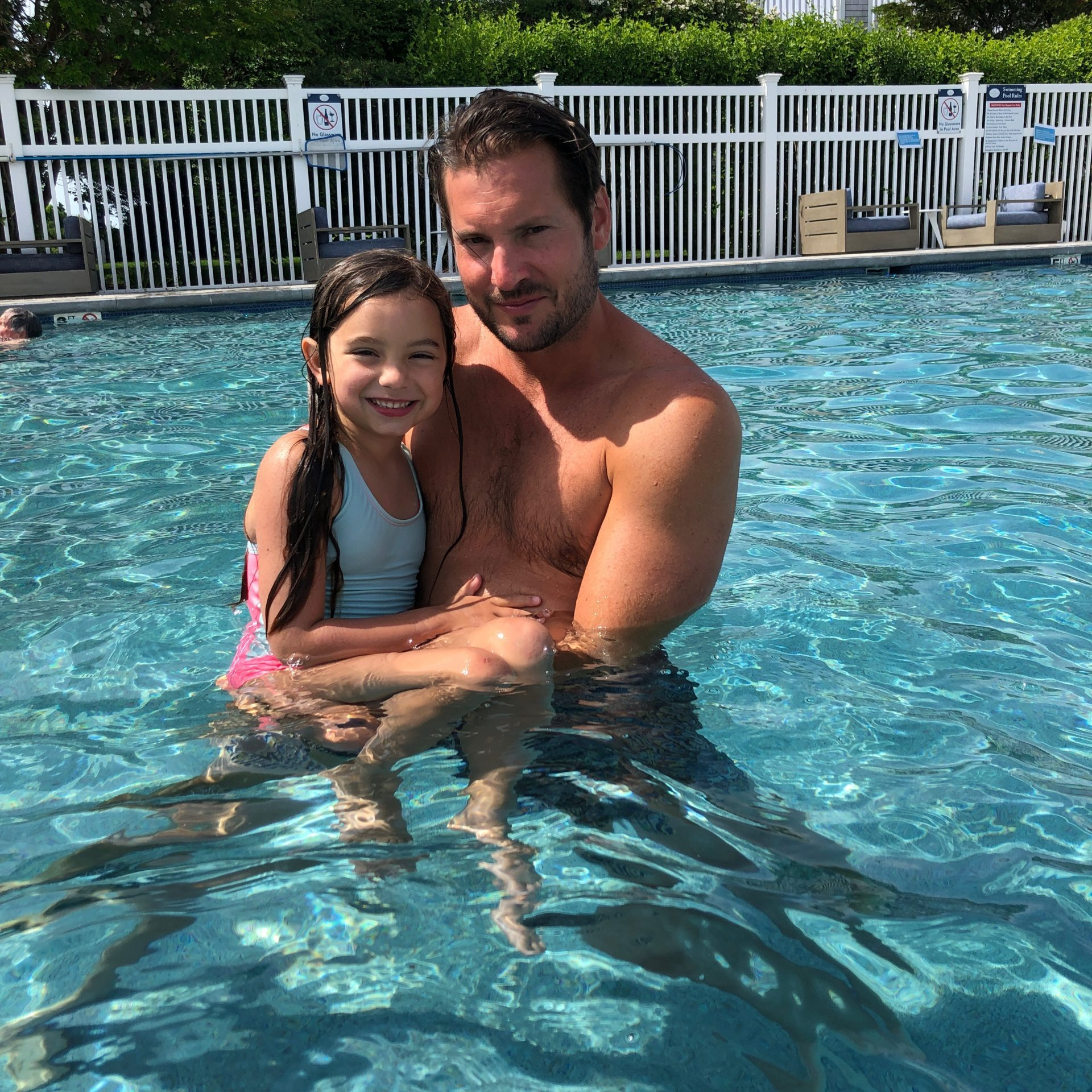 Dad holding little girl in the pool
