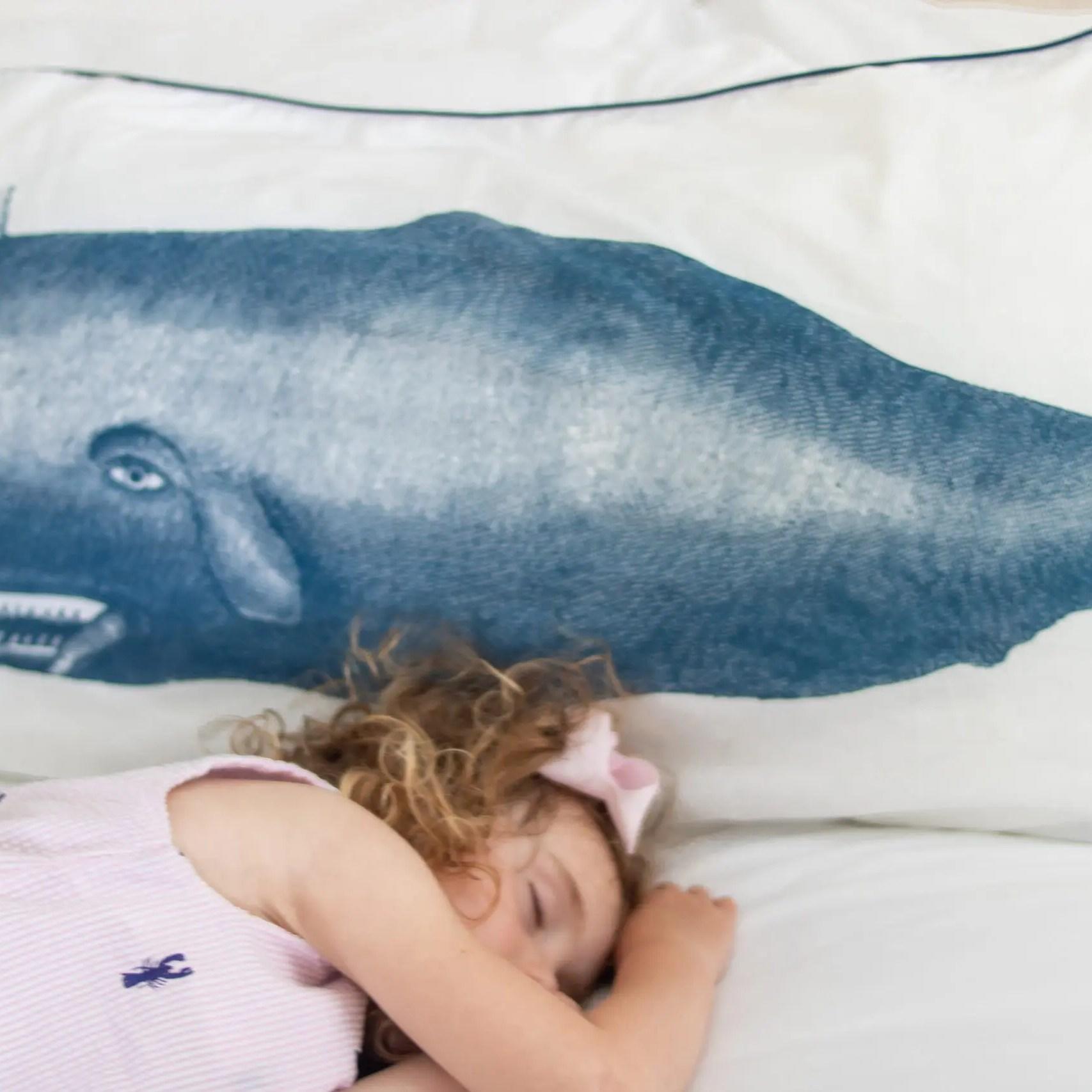 little girl sleeping on bed near Nantucket whale pillow