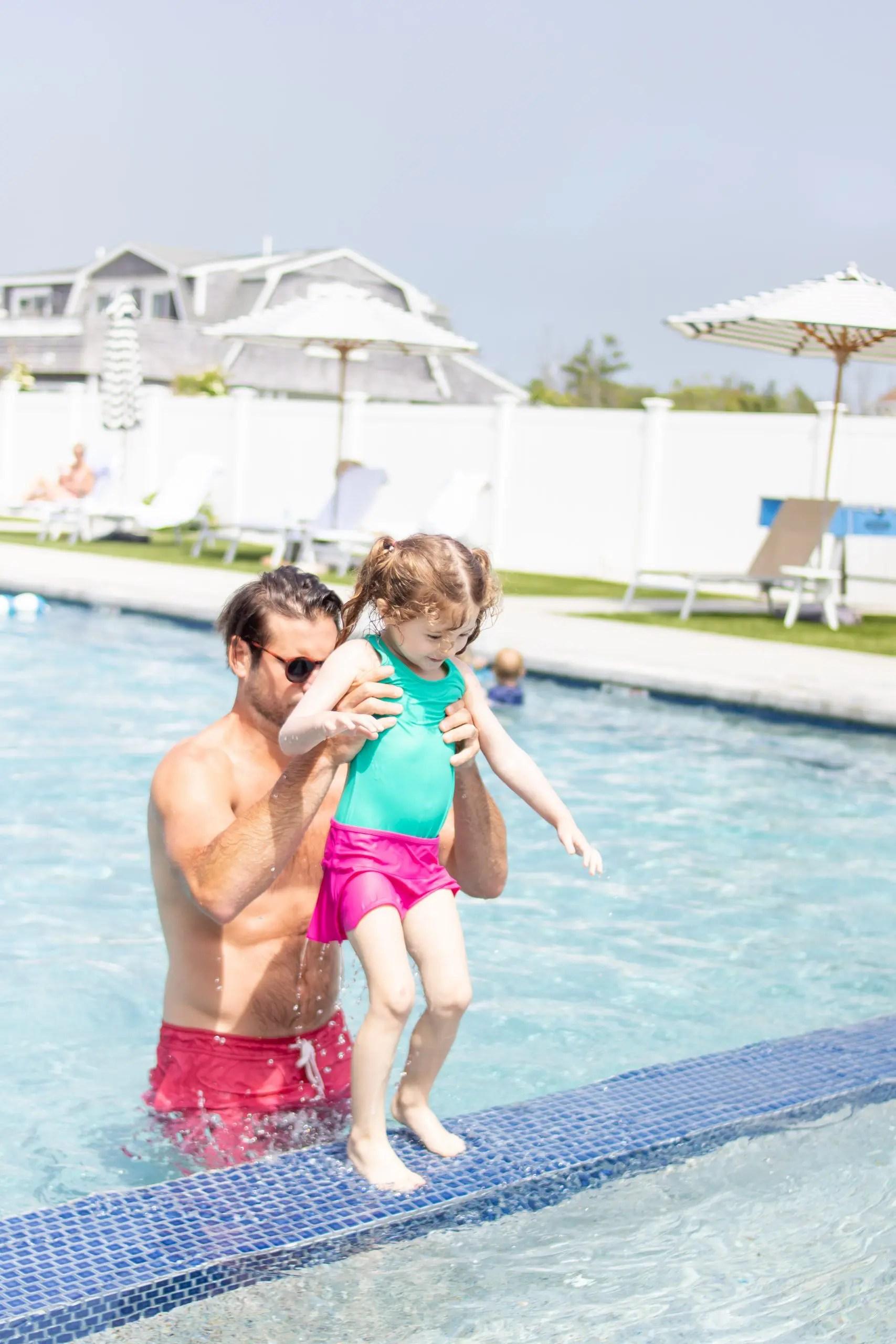dad and little girl swimming in the pool winnetu
