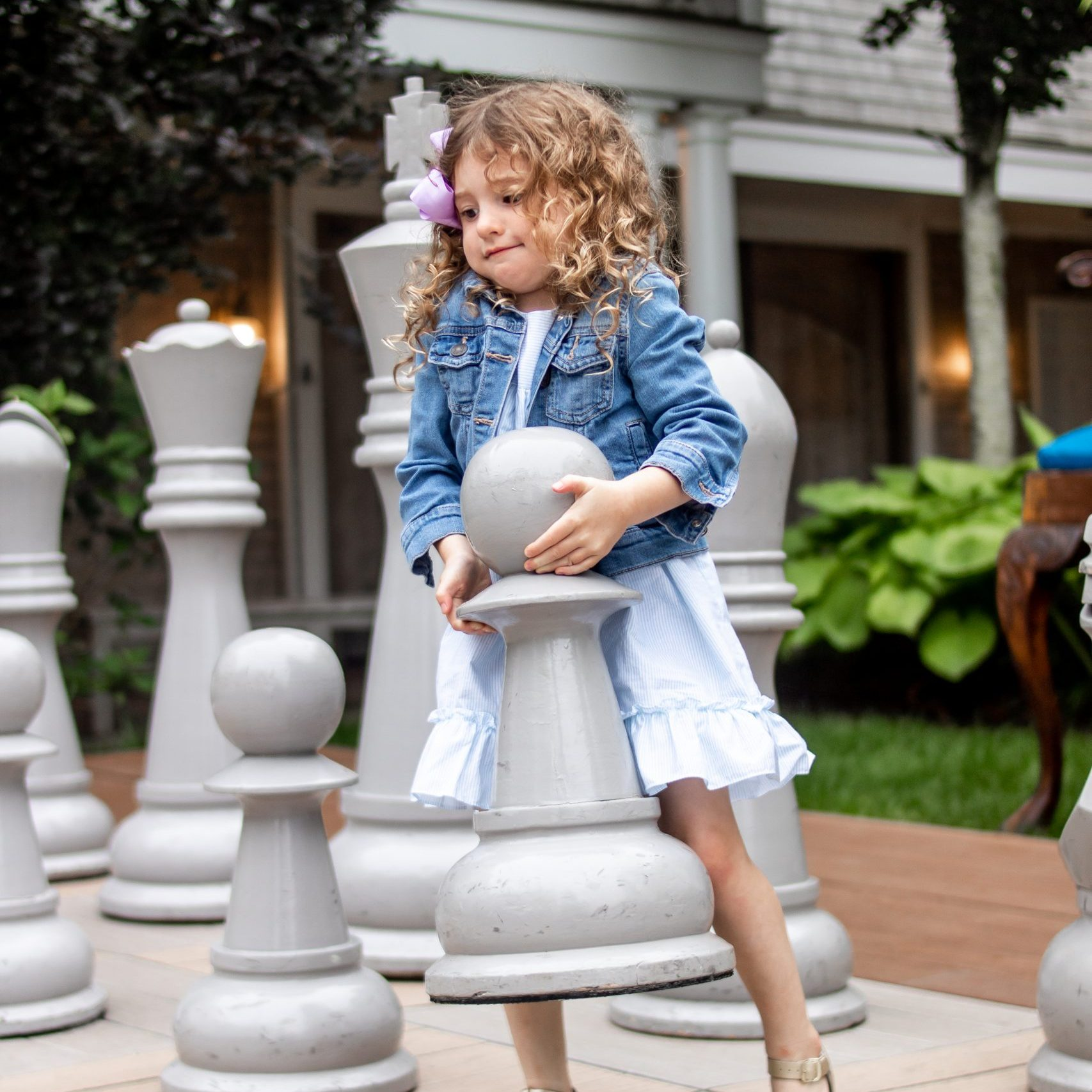 little girl moving giant chess piece