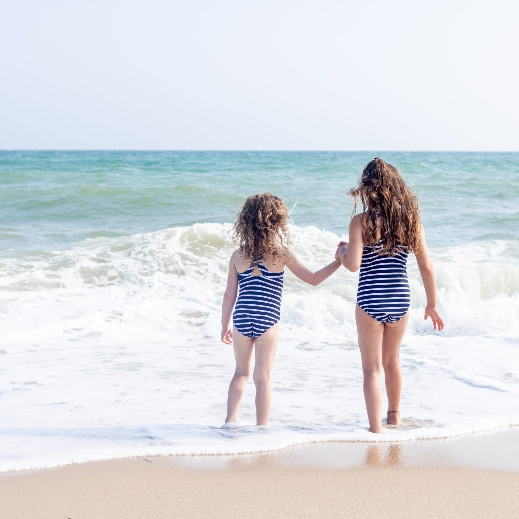 sisters holding hands at the beach