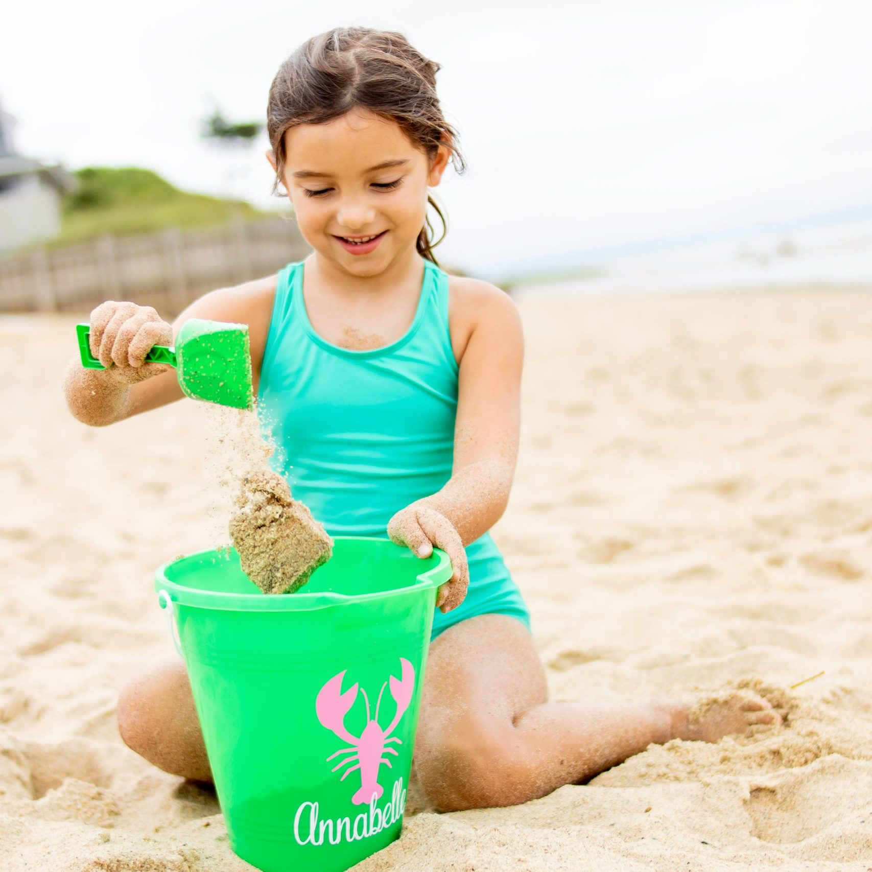 little girl pouring sand in bucket on Cape Cod beach