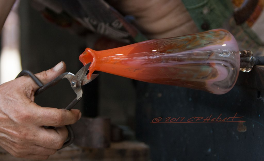 Here, the artist trims the soft molten glass from the top of the mug. As a piece drops to the floor, it hardens and breaks as it strikes the floor.