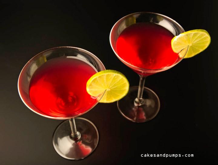 Een Cosmopolitan cocktail gefotografeerd tegen een zwarte achtergrond