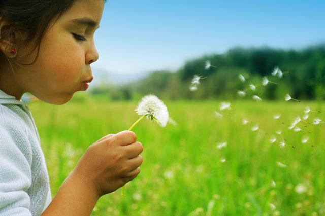 girl-blowing-flower