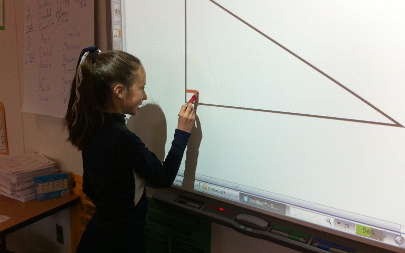 Reagan Elementary student Morgan Polley identifies a right angle with an interactive whiteboard. Going paperless and using more technology are cited by principal Robb Christopherson as ways to reduce costs and teach more effectively.