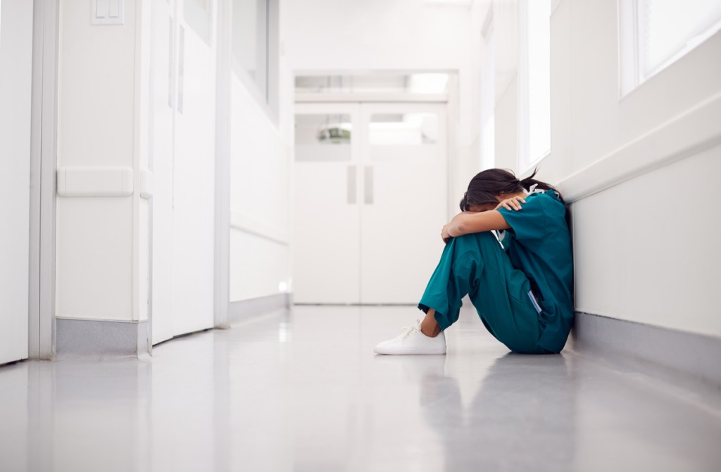 Stressed And Overworked Female Doctor Wearing Scrubs Sitting On Floor In Hospital Corridor