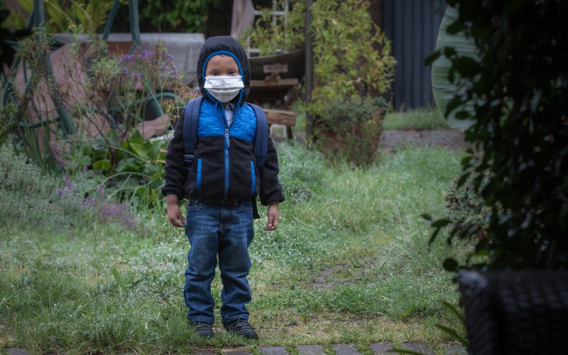 A young boy wearing a backpack, face mask, hoodie jacket, and rain boots, standing outdoors while its raining.