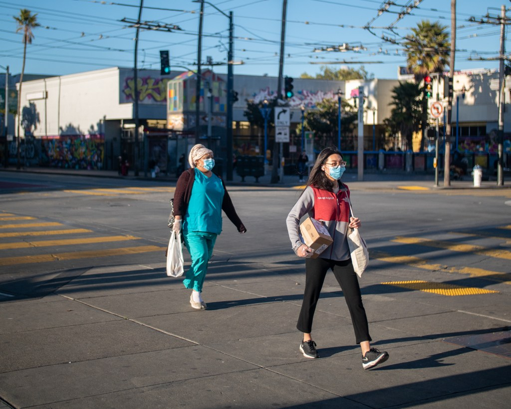 Two women wearing protective masks walking at crosswalk on 16th Street in the Mission District of San Francisco.