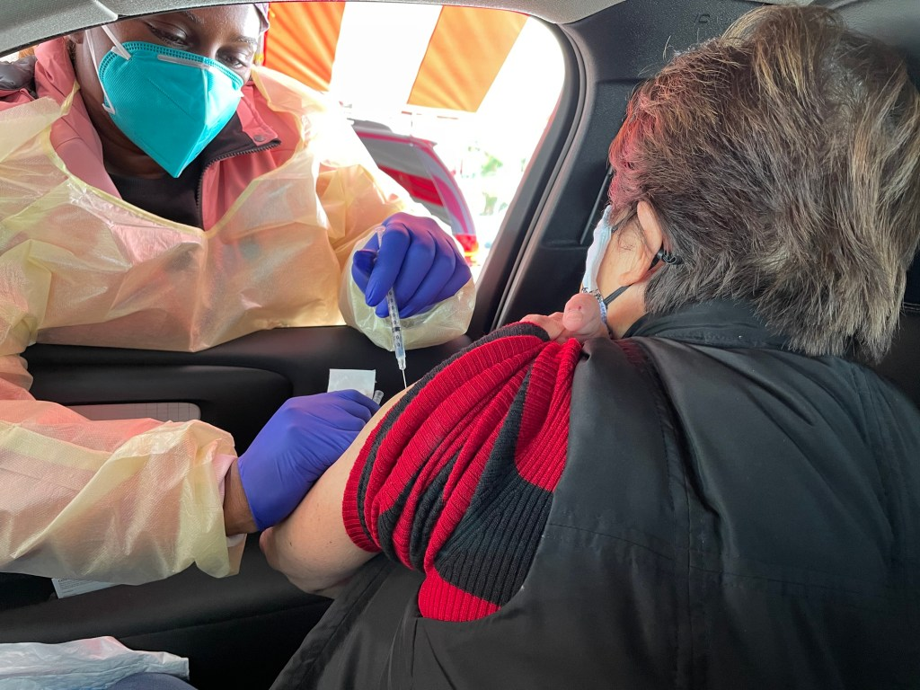 A nurse gives a COVID-19 vaccination at The Forum in Los Angeles in January.