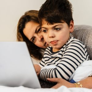A five-year-old boy with a disability is with his mother in the parents' bedroom, sitting on the bed. They look at a laptop.