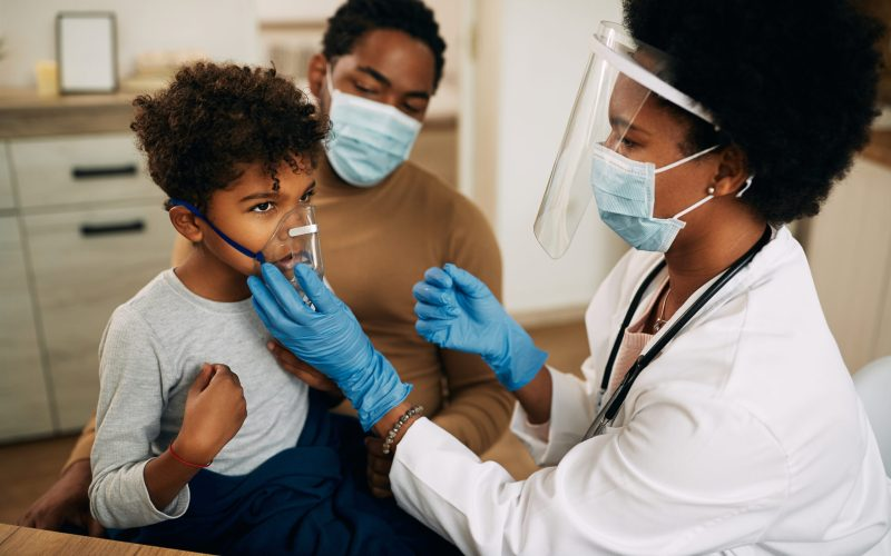 Small black boy receiving asthma treatment while doctor is vising him at home due to COVID-19 pandemic.