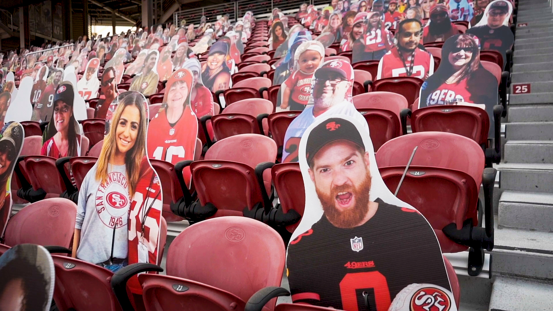 large cut-out photos of fans sit in red stadium seats
