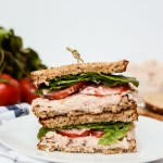 A Quick-and-Healthy Tuna Salad Sandwich cut in half on a plate with produce behind it.
