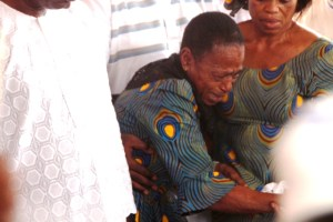 Sister of the deceased is inconsolable at the graveside
