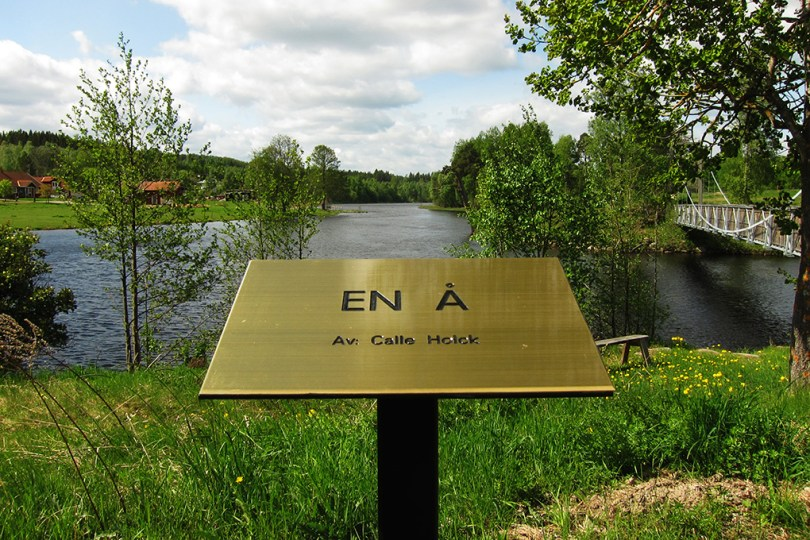 """7 epic sculptures - a sign in front of the art work """"a river - by: Calle Holck"""" and behind the sign is a real river."""