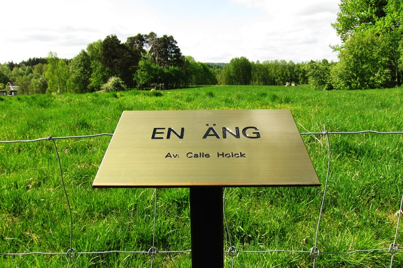 "7 epic sculptures - a sign in front of the art work ""a meadow - by: Calle Holck"" and behind the sign is a real meadow."