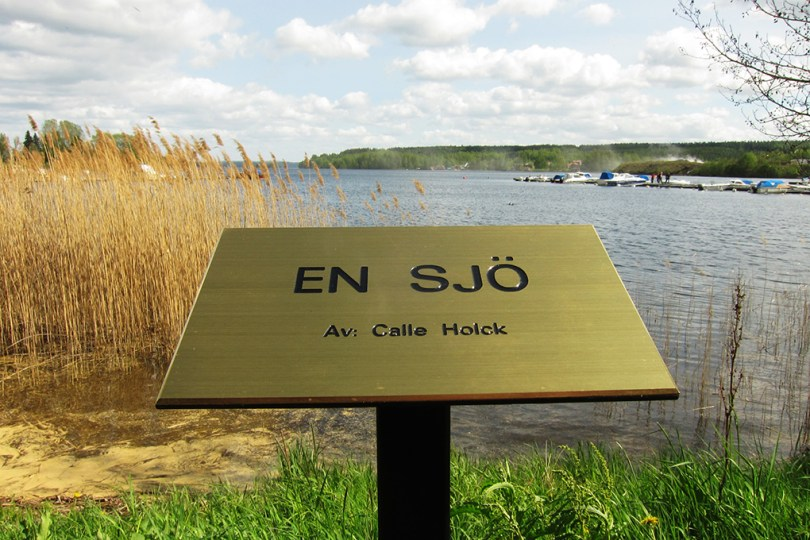 """7 epic sculptures - a sign in front of the art work """"a sea - by: Calle Holck"""" and behind the sign is a real sea."""