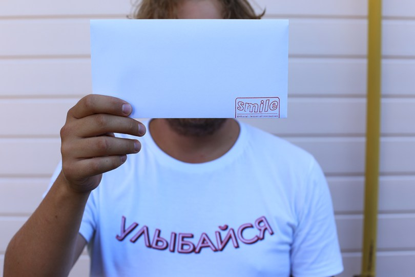"A person is holding up an envelope. At the bottom there is a red stamp that says ""smile""."