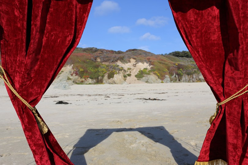 A drop curtain (like one from a theater stage) detached from the stage. Here you can see a beach and a hill when looking through it.